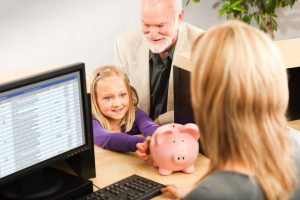 A cheerful grandparent helping a smiling young girl grandchild with her piggy bank savings. Opening a children bank account with the bank teller in a retail bank counter.