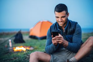 Smiling man resting next to his campfire in the mountain in the evening and texting, with copy space