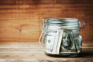 Dollar bills in glass jar on rustic table. Saving money concept.