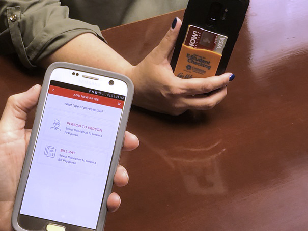 Two smartphone users, one phone has the Cumberland Security Bank mobile app displayed on the screen showing the person to person payment feature