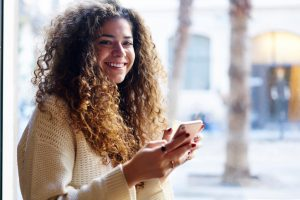 Portrait of cheerful beautiful young woman with curly hair looking at camera spending time in cafe on blurred promotional background holding phone connected to wifi for blogging in social networks