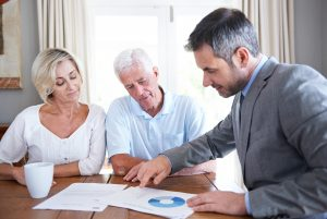 Shot of a financial advisor visiting a senior couple in their home