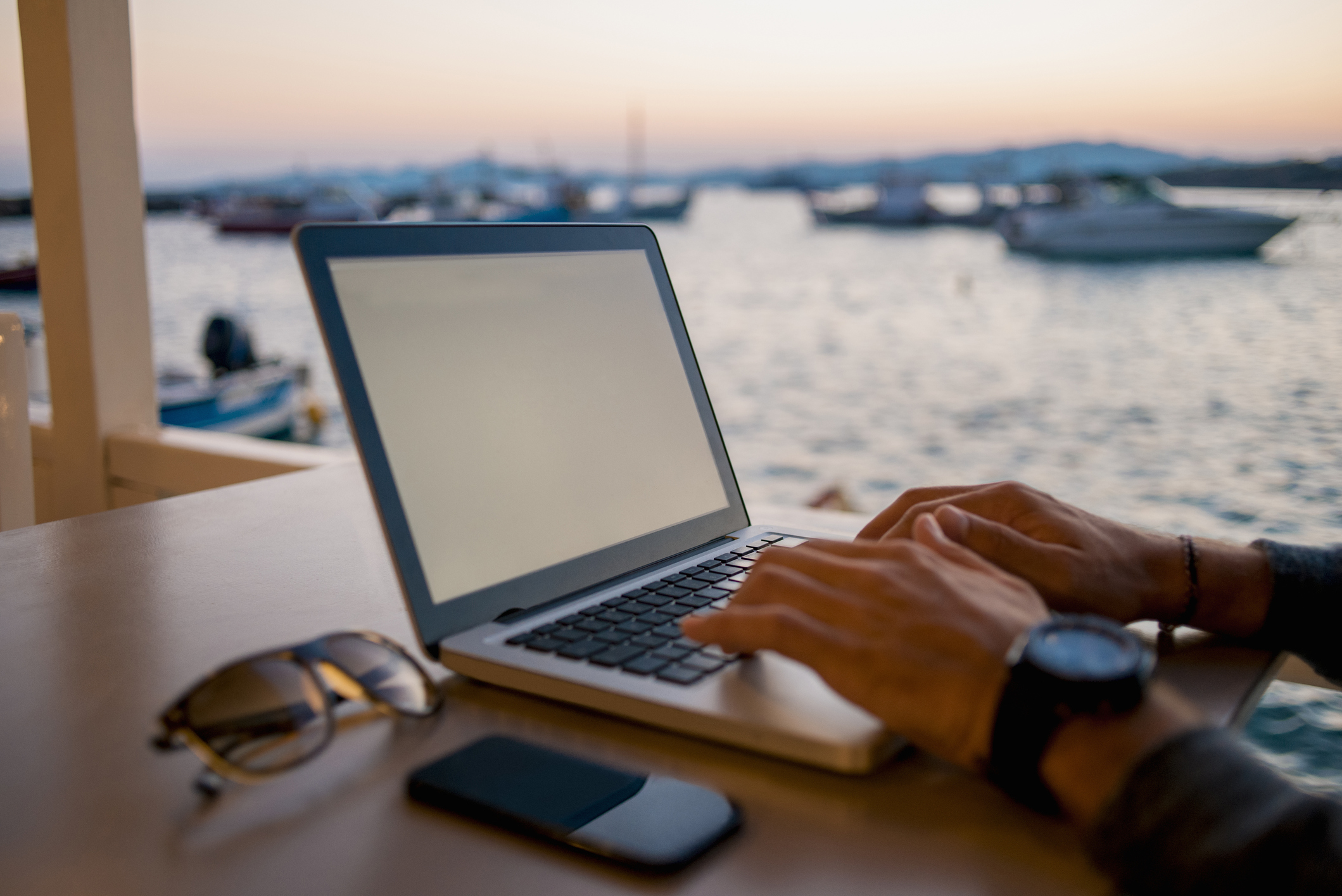 close up photo of man hands working on laptop,in the background is the sea and boats