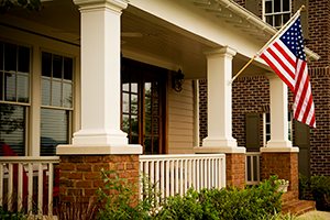 font of a house with white columns and an American flag hanging of off it